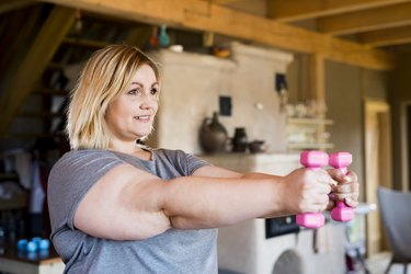 """woman lifting pink dumbbells to tone """"flabby"""" arms in basement"""
