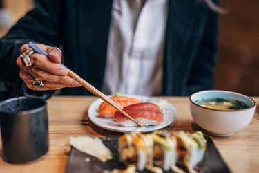Man's hand showing man eating sushi in sushi bar
