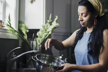 Woman washing food in colander standing at kitchen sink