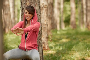 Woman squatting against a tree in the park