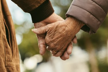 Elderly couple holding hands and in a happy relationship, as an example of healthy aging habits