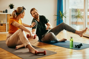 a couple doing strength training for beginners exercises and laughing at home