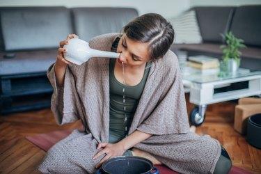 woman using neti pot to stop post-nasal drip