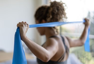Woman using a resistance band for infraspinatus stretching exercises