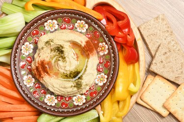 A plate of hummus with olive oil, spices and vegetables.
