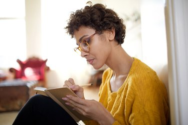 A young woman practices gratitude by writing in a journal