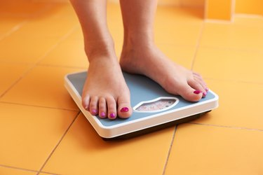 Pair of female feet on a bathroom scale to represent weight loss statistics