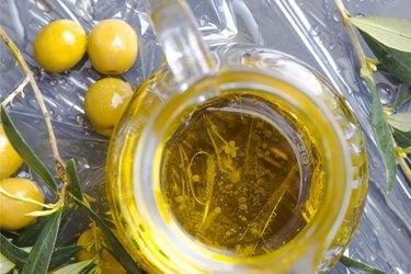overhead shot of jar of extra virgin olive oil with olives