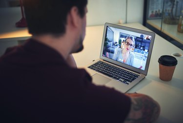 A man sits at a desk while video chatting with a woman through a laptop