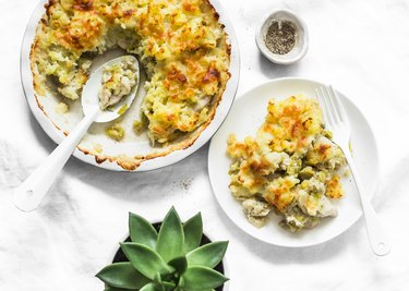 Creamy chicken breast, cauliflower, leek pie with crispy potato cheese topping on light background, top view