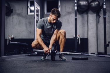 young caucasian man setting up a barbell for a landmine leg workout in the gym.