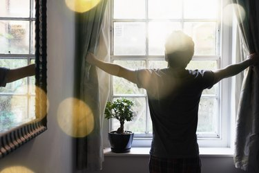 A man opening the curtains in the morning to get sunlight, so he can get better sleep at night
