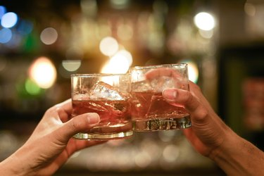 two hands clinking glasses of whiskey drink alcohol beverage together at counter in the pub