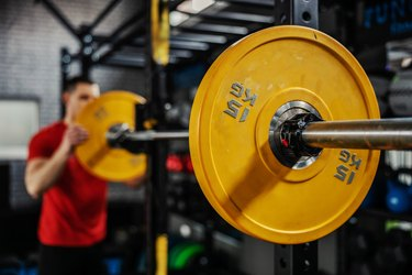 man setting up barbell in a power rack, avoiding the barbell mistake of not using weight clips