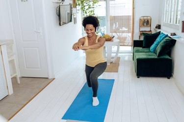 African American woman doing lunges on yoga mat in living room while wearing headphones