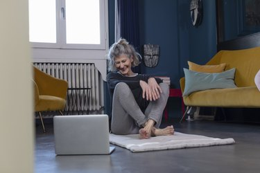 smiling senior woman watching on laptop while sitting at home, trying exercises for getting up from the floor