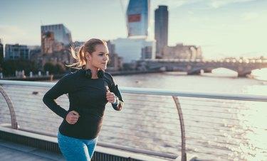 woman in blue leggings running along waterside