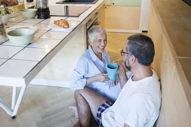 mature caucasian man and woman sitting on the floor drinking from mugs