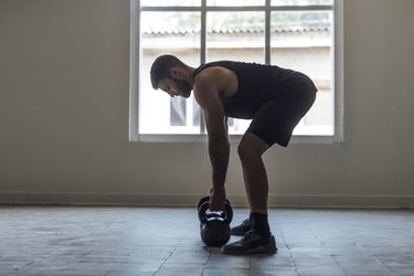 Man Exercising With Kettlebells, cross training Concept