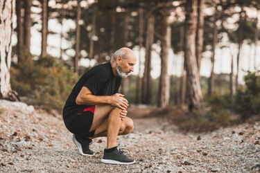 Man experiencing knee pain while running outdoors in the forest