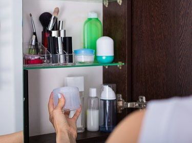 a person in front of a medicine cabinet picking up a bottle of witch hazel, as a natural remedy for hemorrhoids
