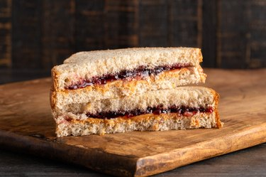 A Peanut Butter and Grape Jelly Sandwich on a Wooden Cutting Board, as an example of food to gain weight for females