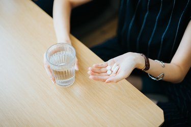 Close up of woman holding NSAIDs painkillers and a glass of water