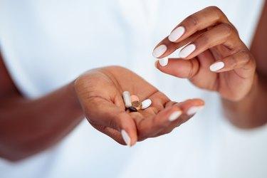 Woman's hands holding multivitamin pills