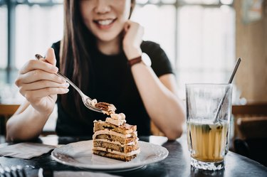 Beautiful smiling young Asian woman having cake and iced tea relaxing and enjoying the moment in the afternoon in the cafe