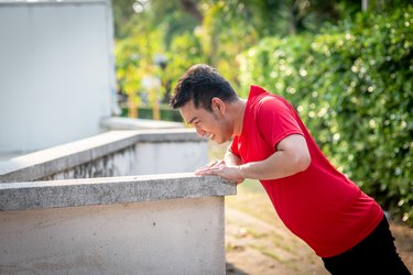 Man doing elevated push-ups against a wall in the park outdoor.
