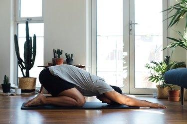 man doing yoga exercise at home on yoga mat