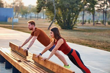 man and woman doing incline plank on park bench
