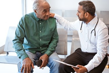 Doctor consoling sad senior male patient with prostate cancer