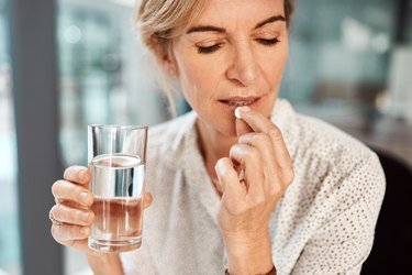 Older woman taking vitamin with glass of water in hand