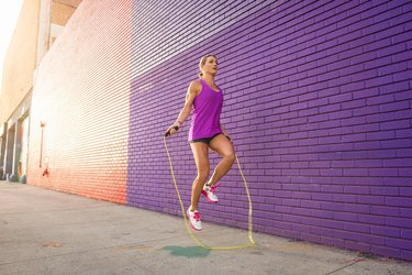 woman in black shorts and purple tank top jumping rope with the best jump rope on sidewalk