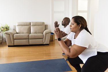 black man and woman practicing mobility exercises for healthy aging in their living room