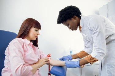 lab technician taking blood for phospholipid and triglyceride tests