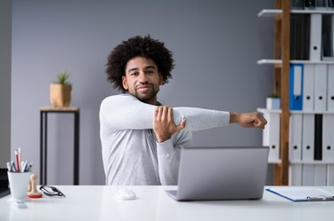 black businessman doing desk stretches in his home office