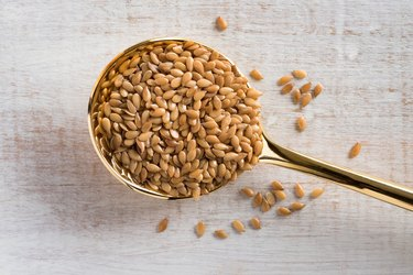 Whole Golden Lignan-rich Flaxseeds on a Gold Spoon