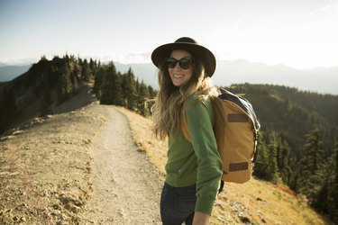 A woman on a day hike wearing a hat and sunglasses as a natural remedy for allergies