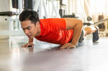 Muscular bodybuilder guy doing push ups exercise  in fitness gym . young sport asian man training . workout