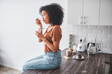 woman sitting on kitchen counter and eating yogurt, as a natural remedy for gas
