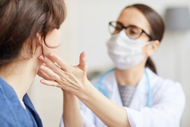 A doctor examining a patient's scalloped tongue