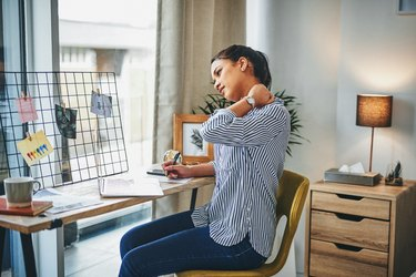A woman rubs her neck at her desk