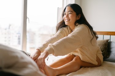 young Asian woman stretching her legs in bed in the morning