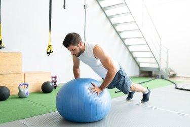 Active Man Doing Swiss Ball Push-Ups At Health Club