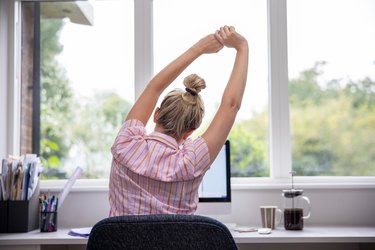 Rear View Of Woman Working From Home and stretching her back