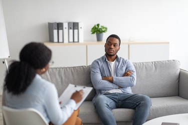 person sitting on a grey couch talking to therapist