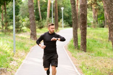 man wearing black long sleeve top and shorts running outside checking heart rate on fitness tracker