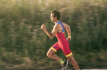 Middle-aged man in sports uniform runs alone in triathlon event. Motion blur